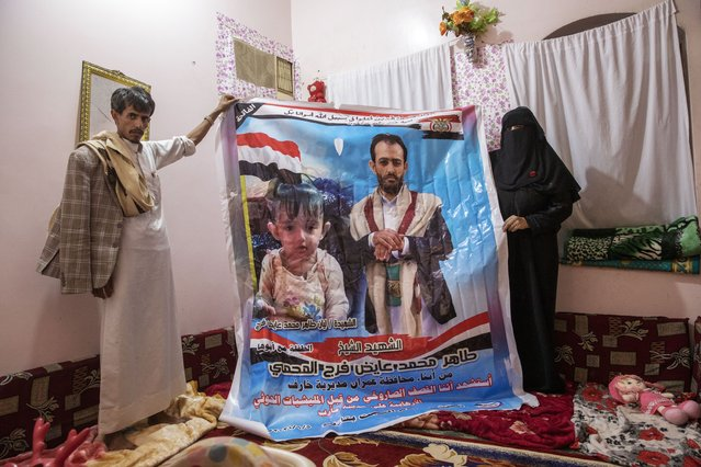 Gamila Salih Ali, right, and Ahmed Farag, mother and uncle of two-year-old Liyan Taher, seen in poster at left, who was killed with her father 32-year-old Taher Farag, seen in poster at right, in a ballistic missile and an explosive-laden drone fired by Yemen's Houthi rebels that hit a fuel station on June 5, 2021 in Rawdha neighborhood, show a poster with photos of them at their home in Marib, Yemen, Saturday, June 19, 2021. (Photo by Nariman El-Mofty/AP Photo)