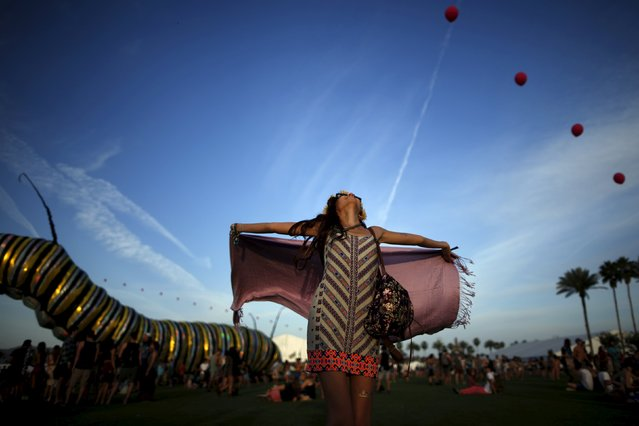 """Melissa Gasia, 24, dances in front of an artwork called """"Papilio Merraculous"""" by Poetic Kinetics at the Coachella Valley Music and Arts Festival in Indio, California April 10, 2015. (Photo by Lucy Nicholson/Reuters)"""