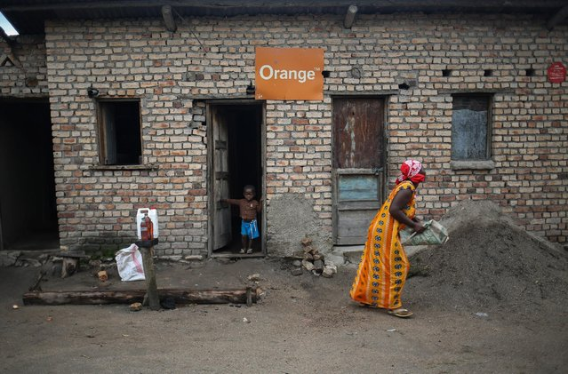 A Bahavu woman and her son stand in front their house which has an Orange sign above the door in Bugarula village on Idjwi island in the Democratic Republic of Congo, November 26, 2016. (Photo by Therese Di Campo/Reuters)