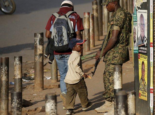 A boy looks at an Ugandan soldier in Kampala, Uganda February 20, 2016. (Photo by Goran Tomasevic/Reuters)