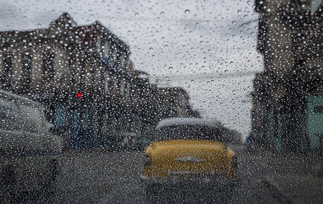 In this May 24, 2018 file photo, rain drops accumulate on a car's windshield as commuters wait at a red light in Havana, Cuba. (Photo by Desmond Boylan/AP Photo)