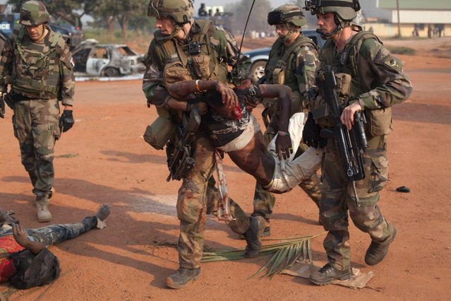 French soldiers evacuate young men wounded by passing Chadian troops during a protest outside Mpoko Airport in Bangui, Central African Republic, Monday, December 23, 2013. (Photo by Rebecca Blackwell/AP Photo)
