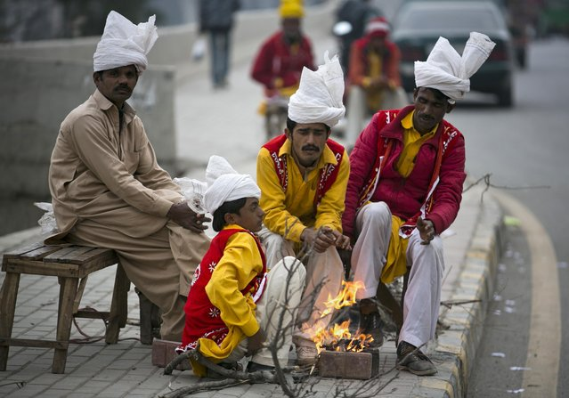 Pakistani street performers sit around fire waiting for customers on a chilly evening in Rawalpindi, Pakistan, Wednesday, February 10, 2016. (Photo by B.K. Bangash/AP Photo)