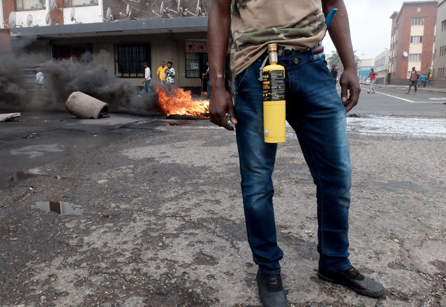 In this photo taken Tuesday, April 14, 2015, an immigrant armed with a petrol bomb on a Durban, South Africa, street during clashes with police and in search of locals that attacked foreign shop owners in the city center. (Photo by Tebogo Letsie/AP Photo)