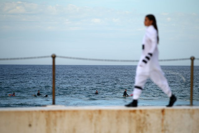 A surfer looks on as a model walks the runway during the Ten Pieces show at Mercedes-Benz Fashion Week Australia 2015 at Bondi Icebergs on April 16, 2015 in Sydney, Australia. (Photo by Mark Nolan/Getty Images)