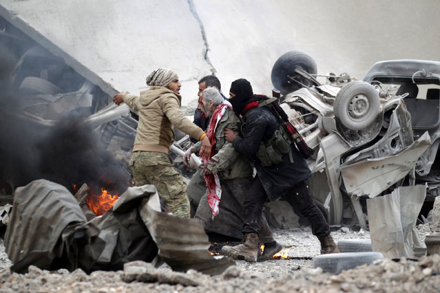 Rebel fighters help an injured man after a car bomb explosion in Jub al Barazi east of the northern Syrian town of al-Bab, Syria January 15, 2017. (Photo by Khalil Ashawi/Reuters)