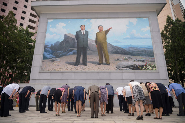 People bow before a portrait of the late leaders Kim Il-sung and Kim Jong-il on the 27th anniversary of the former's death in Pyongyang, North Korea on July 9, 2021. (Photo by Kim Won Jin/AFP Photo)