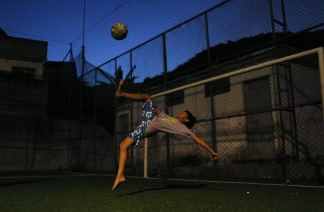 A boy makes an overhead kick at a slum in Rio de Janeiro, May 2, 2014. (Photo by Pilar Olivares/Reuters)
