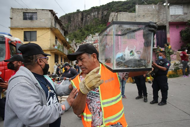 A man evacuates a turtle during search and rescue efforts at the site of a landslide that brought tons of massive boulders down on a steep hillside neighborhood, in Tlalnepantla, on the outskirts of Mexico City, Saturday, September 11, 2021. A section of the peak known as Chiquihuite gave way Friday afternoon, plunging rocks the size of small homes onto the densely populated neighborhood. (Photo by Ginnette Riquelme/AP Photo)