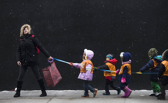 A school teacher, who wished to stay unidentified, attempts to catch snowflakes while leading her students to a library from school in the Harlem neighborhood, located in the Manhattan borough of New York on January 10, 2014. (Photo by Adrees Latif/Reuters)