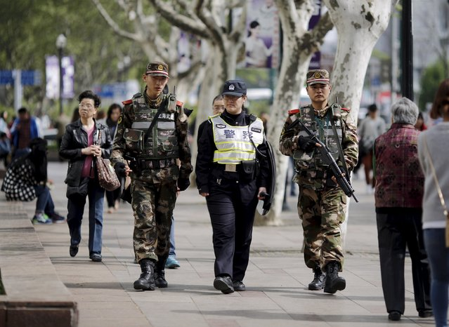 A police officer and armed soldiers patrol the area where two people were injured in a knife-wielding attack near People's Square in central Shanghai April 17, 2015. (Photo by Carlos Barria/Reuters)