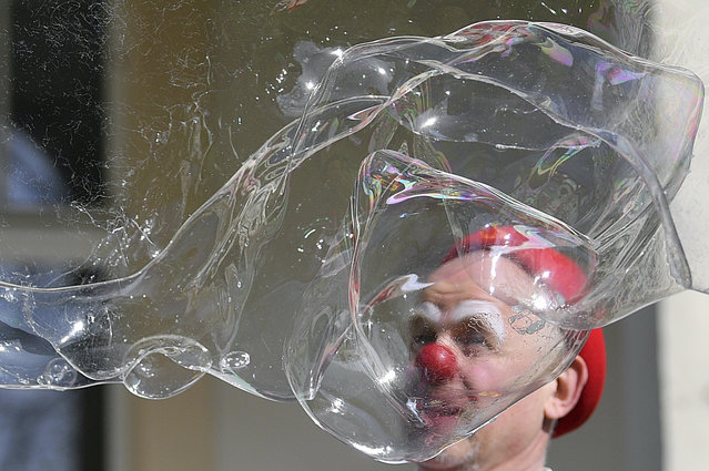 """Clinic clown """"Herr Liebling"""" plays with soap bubbles in front of the windows of the kidney centre for children and adolescents at the St. Georg Clinic in Leipzig, Germany, Wednesday, April 15, 2020. The clown performance is the first since the corona-related restriction. For about one and a half years now, the clinic clowns Heiko Fischer and Marita Brauer, as they are called by their real names, have been performing at the children's clinic, normally twice a month. With a safe distance they now make the little patients laugh in front of the windows. (Photo by Hendrik Schmidt/dpa via AP Photo)"""