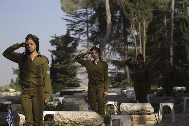 Israeli soldiers salute as they stand next to graves of fallen soldiers during a ceremony at the Mount Herzl military cemetery in Jerusalem, ahead of Memorial Day April 19, 2015. Israel commemorates its fallen soldiers on Memorial Day, which begins Tuesday night. (Photo by Ronen Zvulun/Reuters)