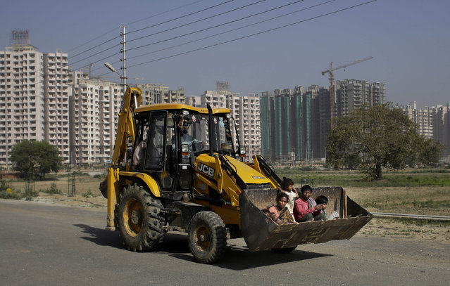 A migrant Indian construction workers' family rides in the bucket of an excavator on Earth Day in New Delhi, India, Wednesday, April 22, 2015. The world marks Earth Day on April 22 to increase awareness and to promote practices for the sustainability and protection of the Earth's natural environment. (Photo by Altaf Qadri/AP Photo)