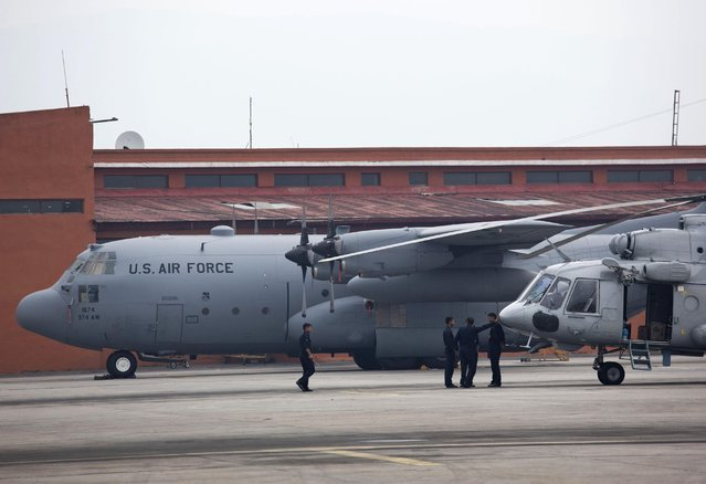 A U.S. Air Force plane, background and an Indian army helicopter are parked on the tarmac of the Kathmandu international airport the day after a massive earthquake devastated the region, in Kathmandu, Nepal, Sunday, April 26, 2015. The U.S. government is working closely with the Nepal government to provide assistance and support, a U.S. Embassy to India press release, Sunday said. (Photo by Bernat Armangue/AP Photo)