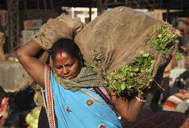 An Indian woman laborer carries a sack of vegetable at a wholesale market on the International Women's Day, in Jammu Tuesday, March 8, 2016. (Photo by Channi Anand/AP Photo)
