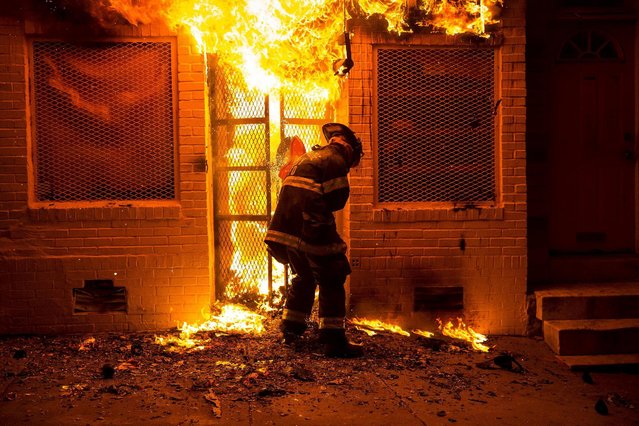 A firefighter uses a saw to open a metal gate while fighting a fire in a convenience store and residence during clashes after the funeral of Freddie Gray in Baltimore, Maryland in the early morning hours of April 28, 2015. (Photo by Eric Thayer/Reuters)