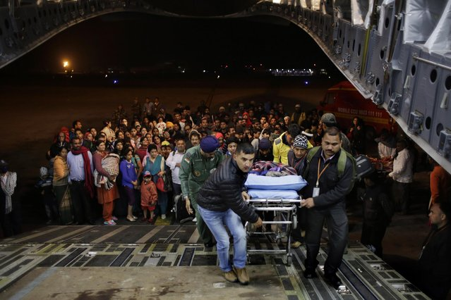 An injured survivor of Saturday's earthquake is carried into a military plane evacuating injured and stranded Indians from Kathmandu to New Delhi during a midnight rescue mission by Indian Air Force, in Kathmandu, Nepal, Wednesday, April 29, 2015. (Photo by Altaf Qadri/AP Photo)