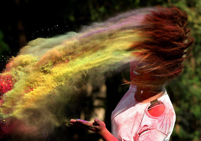 A college girl takes part in the Holi festival celebrations in Bhopal, India, 19 March 2019. Holi is celebrated on the full moon day and marks the beginning of the spring season. Holi will be celebrated as the Hindu spring festival of colors across the country on 21 March. (Photo by Sanjeev Gupta/EPA/EFE)