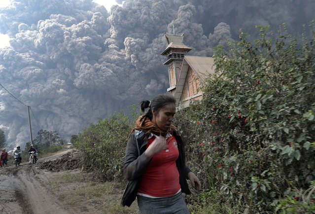 A woman flees as Mount Sinabung erupts near Bekerah village, in Karo district, North Sumatra, on February 1, 2014. Three men were burned and taken to hospital after being engulfed in heat clouds of Mount Sinabung in Indonesia, local officials said. (Photo by Sutanta Aditya/AFP Photo)