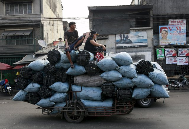 Vendors sit on sacks of coal strapped on a motorcycle cab as they head to a market in Tondo, metro Manila March 1, 2016. (Photo by Romeo Ranoco/Reuters)