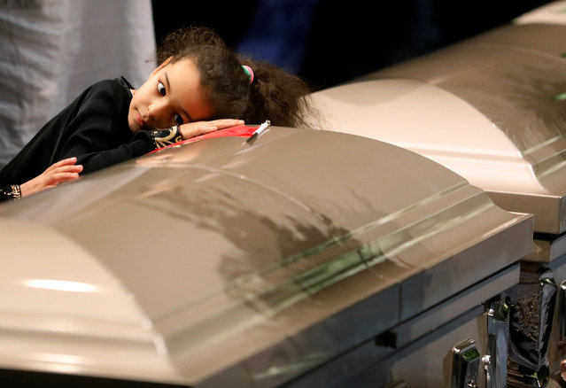 A young mourner lays her head on one of the caskets during funeral services for three of the victims of the deadly shooting at the Quebec Islamic Cultural Centre, at the Congress Centre in Quebec City, Quebec, February 3, 2017. (Photo by Mathieu Belanger/Reuters)