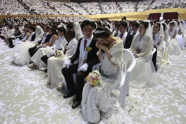 A bride weeps in a mass wedding ceremony at the CheongShim Peace World Center in Gapyeong, South Korea, Wednesday, February 12, 2014. (Photo by Lee Jin-man/AP Photo)