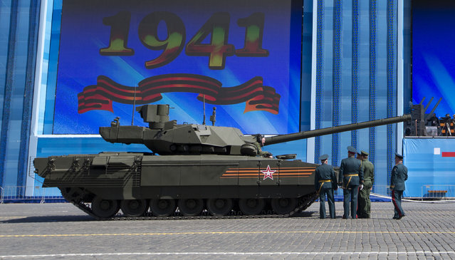 Russian army officers discuss a situation with a crew member of the new Russian T-14 Armata tank at the Red Square during a preparation for general rehearsal for the Victory Day military parade which will take place at Moscow's Red Square on May 9 to celebrate 70 years after the victory in WWII, in Moscow, Russia, Thursday, May 7, 2015. (Photo by Alexander Zemlianichenko/AP Photo)