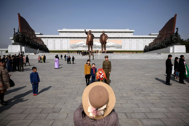 """A family pose for a photo after paying their respects before the statues of late North Korean leaders Kim Il Sung and Kim Jong Il, as part of celebrations marking the anniversary of the birth of Kim Il Sung, known as the """"Day of the Sun"""", on Mansu hill in Pyongyang on April 15, 2019. (Photo by Ed Jones/AFP Photo)"""