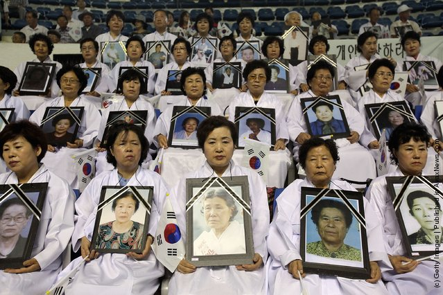 South Korean family members of victims of the World War II hold portrait of their loved one during the 66th Independence Day ceremony in Seoul, South Korea