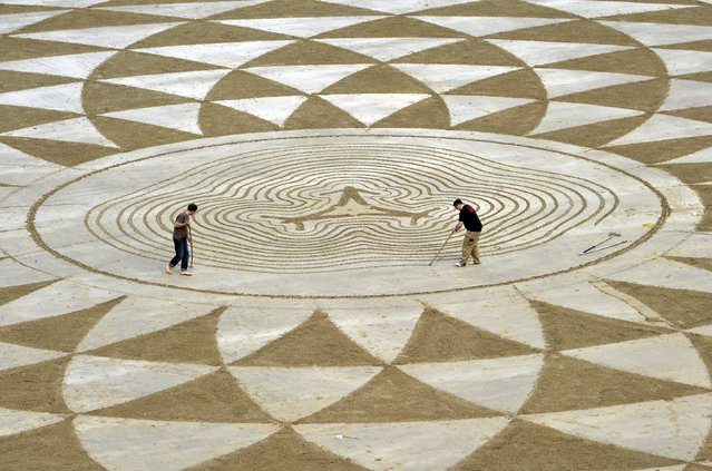 Local artists draw patterns in the sand at low tide on North Beach, Tenby, South Wales, May 7, 2015. (Photo by Rebecca Naden/Reuters)
