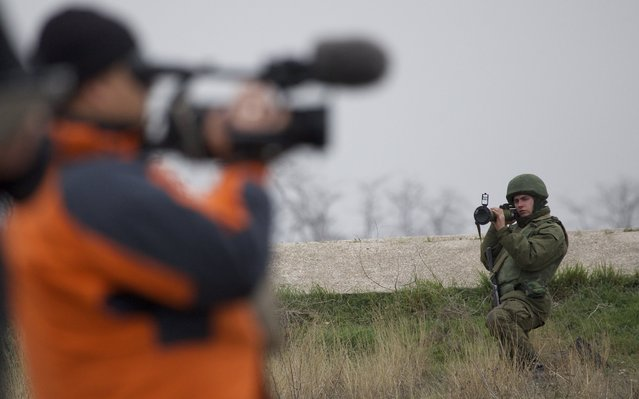 A Russian soldier aims his grenade launcher as  a cameraman films at the Belbek air base, outside Sevastopol, Ukraine, on Tuesday, March 4, 2014. Russian troops, who had taken control over Belbek airbase, fired warning shots in the air as around 300 Ukrainian officers marched towards them to demand their jobs back. (Photo by Ivan Sekretarev/AP Photo)