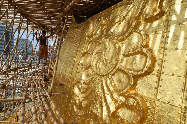 In this photo taken on March 12, 2016, a section of the Sule Pagoda's tower is pictured covered in gold after renovations. The five-yearly renovation of the Sule Pagoda has seen the monument shed its weather-damaged frontage, re-clad in several hundred solid gold plates – each costing around 1,100 USD – and thousands of squares of gold leaf. (Photo by Romeo Gacad/AFP Photo)