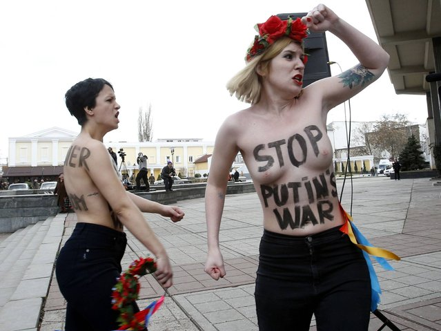 Topless activists from the Ukrainian feminist group Femen hold an anti-war protest near the Crimean parliament building in Simferopol. (Photo by David Mdzinarishvili/Reuters)