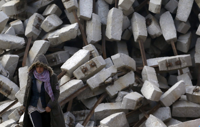 A woman passes rubble as she walks  through the makeshift refugee camp at the northern Greek border point of Idomeni, Greece, Monday, March 28, 2016. (Photo by Darko Vojinovic/AP Photo)