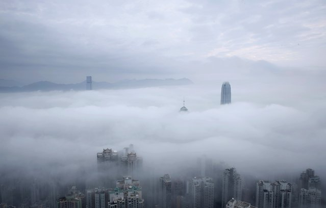 Two International Finance Centre tower, center right, and International Commerce Centre, top left, are seen over the clouds in Hong Kong, Sunday, February 22, 2015. (Photo by Kin Cheung/AP Photo)