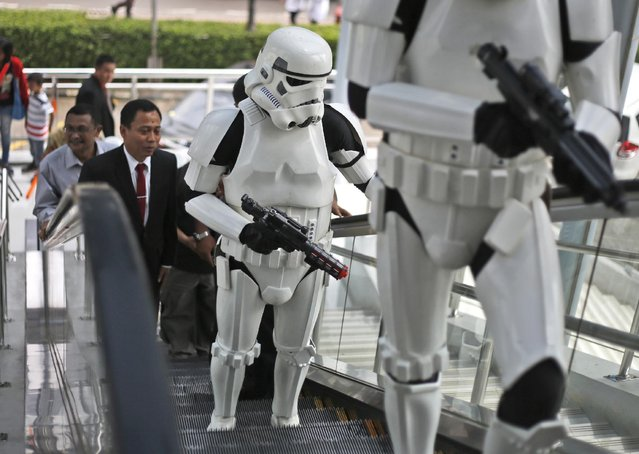 """Indonesian men dressed as """"stormtroopers"""" from the movie """"Star Wars"""" stand on an escalator  during a promotional event at a shopping mall in Jakarta, Indonesia, Tuesday, May 19, 2015. Stormtroopers are fictional soldiers from the epic film series. (Photo by Dita Alangkara/AP Photo)"""