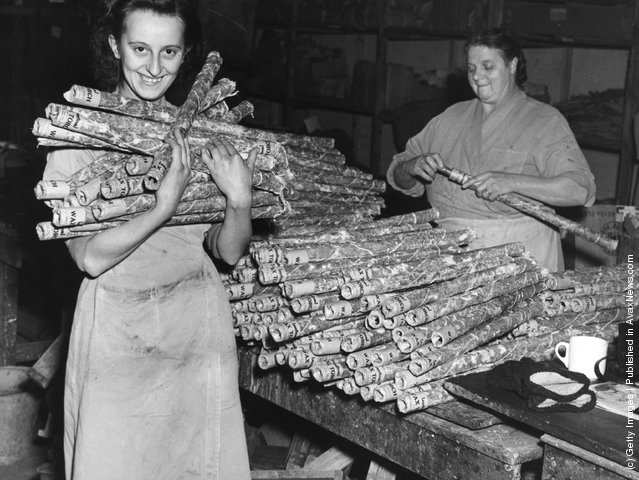 1950: A factory worker holds a bundle of long-burning fog torches at the Brocks firework factory, Hertfordshire
