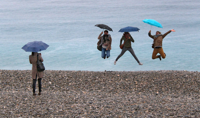Tourists jump for a photo in front of the Mediterranean sea under their umbrellas by a rainy day, on the beach of Nice, southeastern France, Saturday, March 22, 2014. (Photo by Lionel Cironneau/AP Photo)