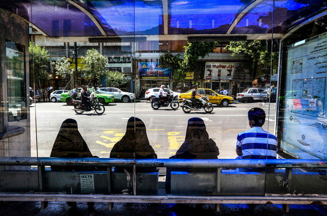 Women sit as they wait for a bus at a stop along a street in the Iranian capital Tehran on May 28, 2019. (Photo by Atta Kenare/AFP Photo)