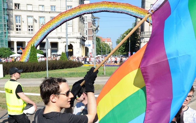 "A  participant waves a multicolor flag in front of a controversial art installation ""The Rainbow""  during the annual gay pride parade in Warsaw, Poland, Saturday, June 13, 2015. Gay rights activists hold their 15th yearly ""Equality Parade"" as Poland slowly grows more accepting of gays and lesbians, but where gay marriage, and even legal partnerships, still appear to be a far-off dream. This year's parade comes amid a right-wing political shift, a possible setback for the LGBT community. (AP Photo/Alik Keplicz)"