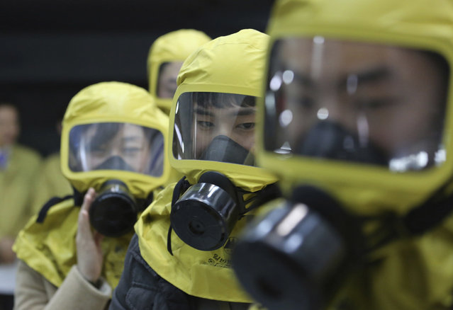 South Korean government officials wearing gas masks attend a civil defense drill against possible North Korea's chemical attack at their office in Seoul, South Korea, Wednesday, March 15, 2017. A nationwide civil defense drill took place Wednesday preparing for possible terror, natural disaster and sudden air attack by North Korea. (Photo by Ahn Young-joon/AP Photo)