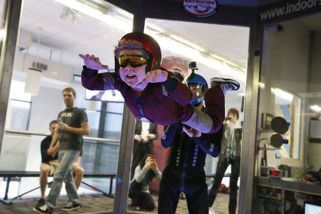Wearing an Iron Man costume, Max Vertin, 7, from Hastings, Neb., floats in a wind tunnel simulating free fall during a day hosted by the Make-A-Wish Foundation at SkyVenture Colorado in Lone Tree, Colo., south of Denver, on Tuesday April 15, 2014. Vertin and his two brothers have Duchenne muscular dystrophy, a rare disease which causes their muscles to slowly deteriorate. Despite his medical condition, his parents say he is a regular kid who likes the color orange, pizza, collecting bugs, and his favorite superhero, Iron Man. (Photo by Brennan Linsley/AP Photo)