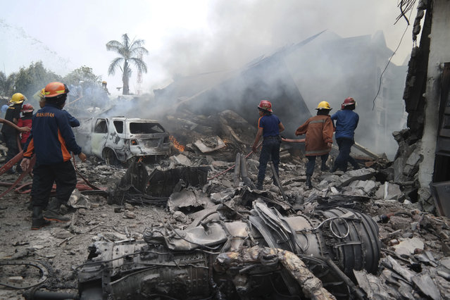 Firemen attempt to extinguish the fire surrounding the wreckage of an Indonesian military transport plane after it crashed in the North Sumatra city of Medan, Indonesia, June 30, 2015. (Photo by Irsan Mulyadi/Reuters/Antara Foto)