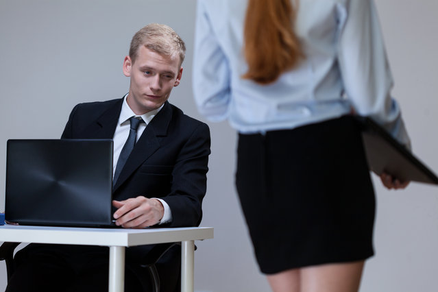 Man observing female co-worker's legs at work. (Photo by Katarzyna Bialasiewicz/Getty Images)