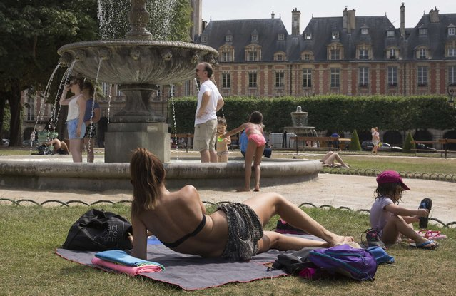 People enjoy the sun and cool down in a fountain on the Place des Vosges in central Paris, France, July 3, 2015. An unusual heat wave sweeps France this week with temperatures which could reach 40 degrees Celsius. (Photo by Philippe Wojazer/Reuters)
