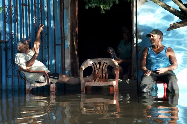 Men sits in a flooded street in Guasdualito, in the state of Apure, Venezuela, July 4, 2015. (Photo by Carlos Eduardo Ramirez/Reuters)