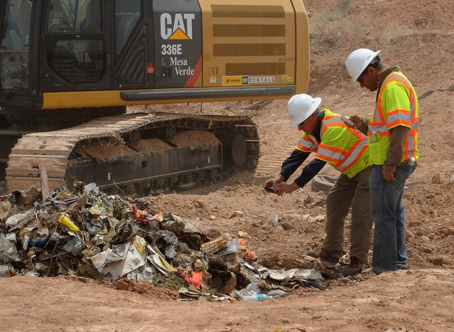 """Workers take photos of recovered Atari games at the old Alamogordo landfill in Alamogordo, New Mexico, April 26, 2014. Documentary filmmakers digging in a New Mexico landfill on Saturday unearthed hundreds of """"E.T. the Extra-Terrestrial"""" cartridges, considered by some the worst video game ever made and blamed for contributing to the downfall of the video game industry in the 1980s. (Photo by Mark Wilson/Reuters)"""