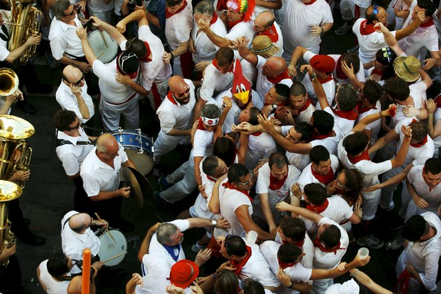 Revellers block the way of the municipal music band as they sing, dance and drink during the traditional Riau-Riau dance from the town hall to the Saint Fermin Chapel at San Lorenzo church on the first day of the San Fermin Festival in Pamplona, Spain, July 6, 2015. (Photo by Susana Vera/Reuters)