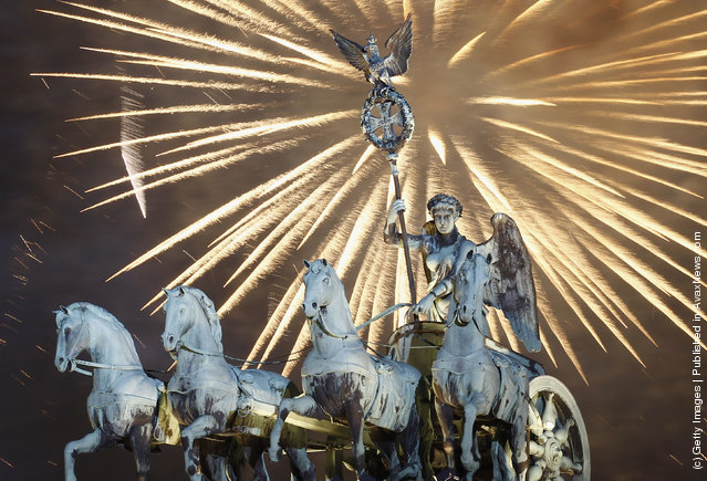 Fireworks explode over the Quadriga statue atop the Brandenburg Gate on New Year's Eve on January 1, 2012 in Berlin